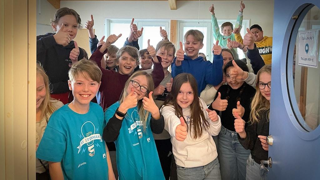 En klass står i en dörröppning och ser glada ut.