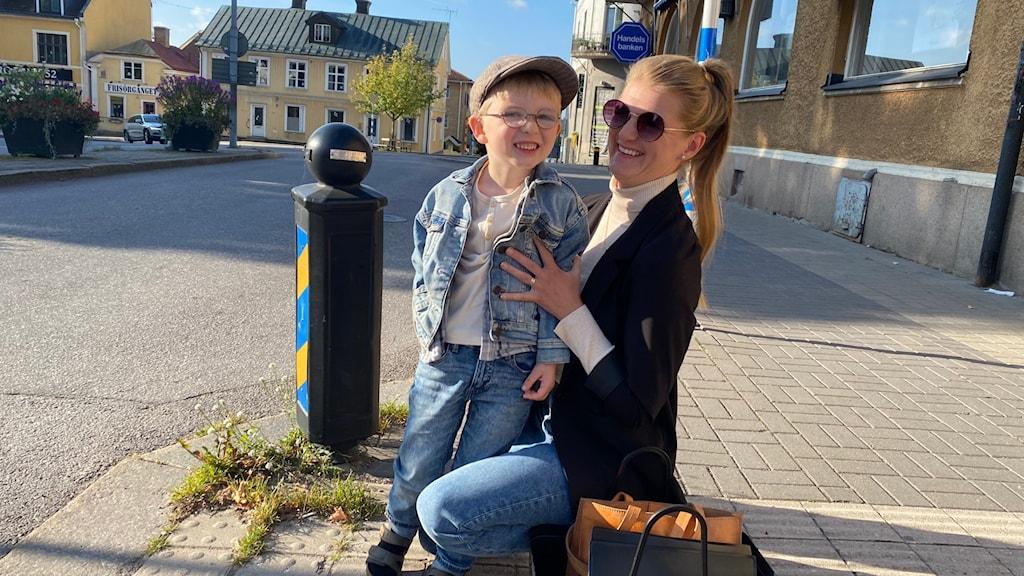 En pojke i jeansjacka, jeans, keps och glasögon tillsammans med sin mamma.