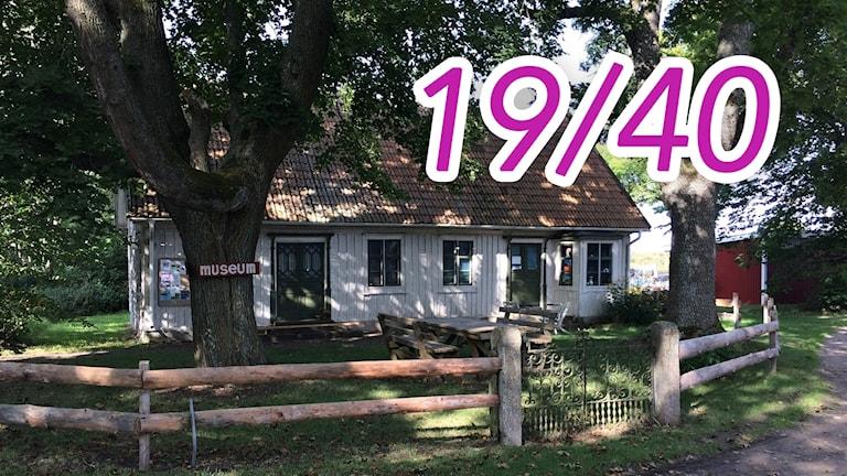 Vit byggnad med rött tegeltak. trästaket kring huset och stort lummigt träd i trädgården.