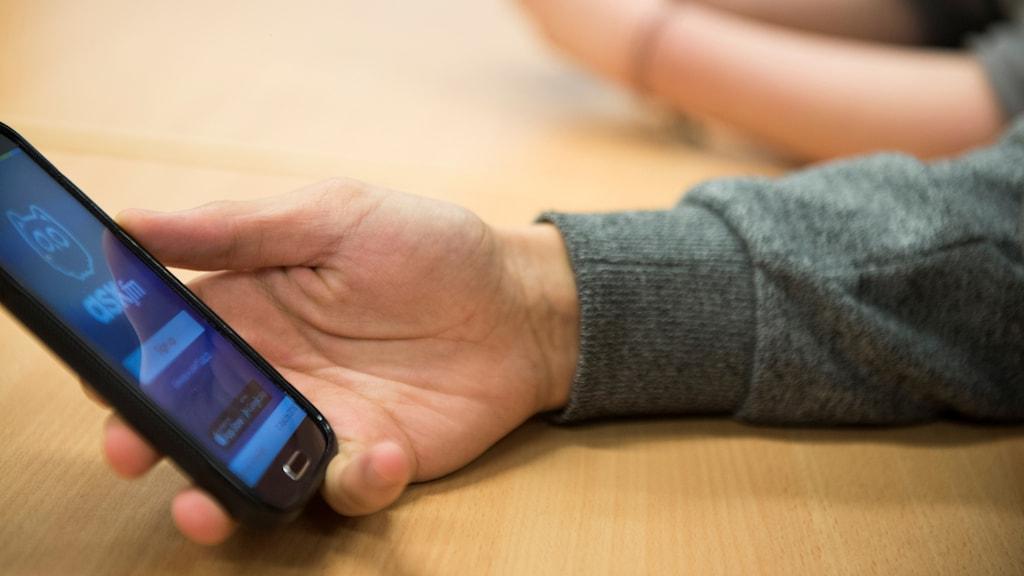 En hand håller en mobiltelefon.