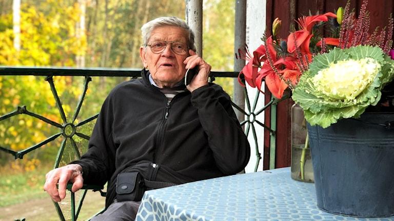 En äldre man som pratar i mobiltelefon.