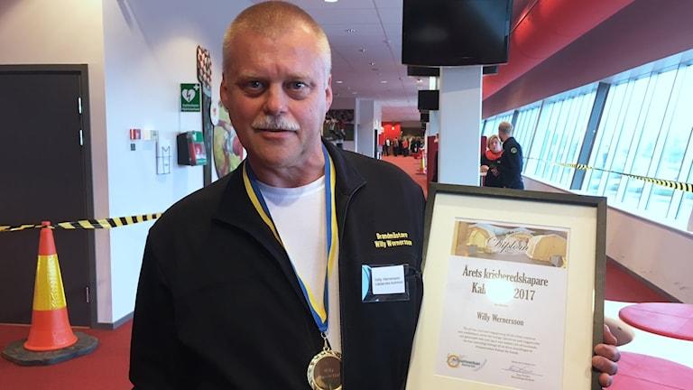 Willy Wernersson håller i ett diplom och har en guldmedalj runt halsen.