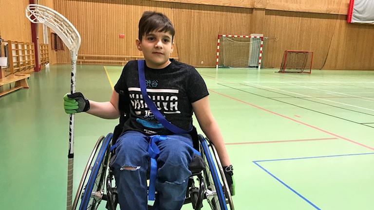 En pojke som sitter i rullstol och håller i en innebandyklubba.