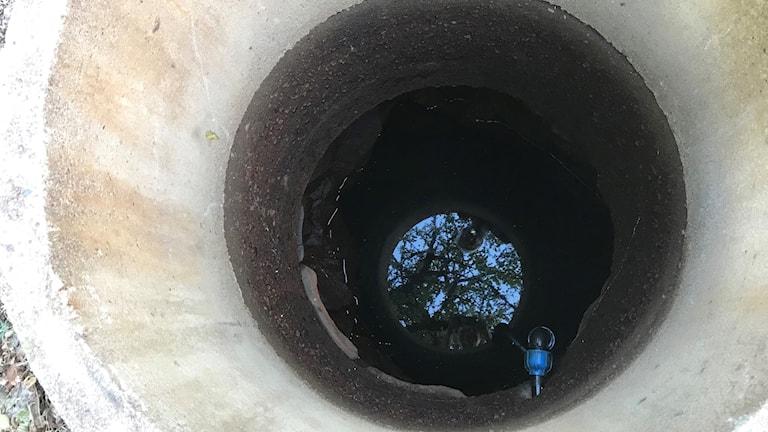 En brunn med väldigt lite vatten längst ner på botten.
