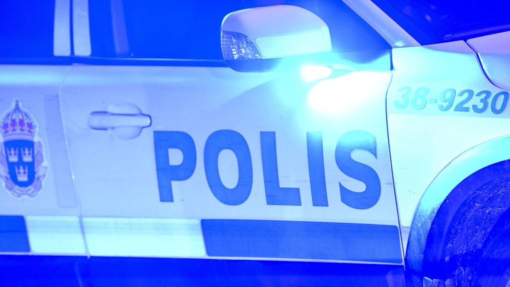 Polisbil på natten med blåljus igång.