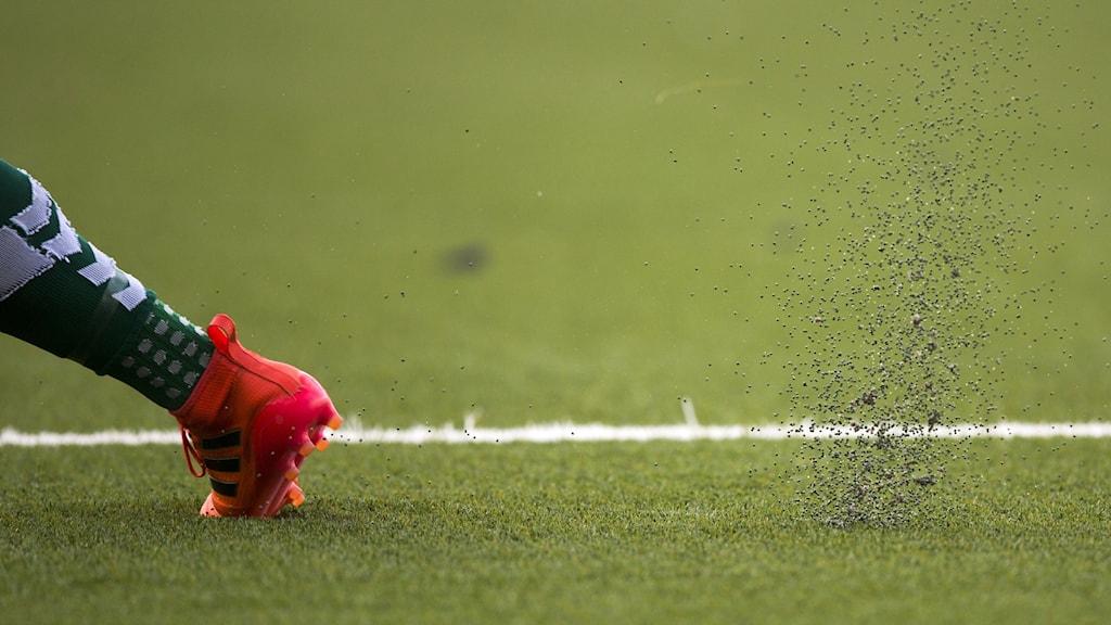 En fotbollsspelares fot sprider plastgranuler på en konstgräsplan.