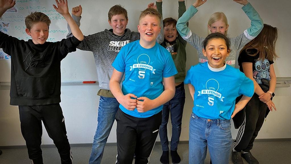 En skolklass står i ett klassrum och sträcker händerna mot taket och ser glada ut.