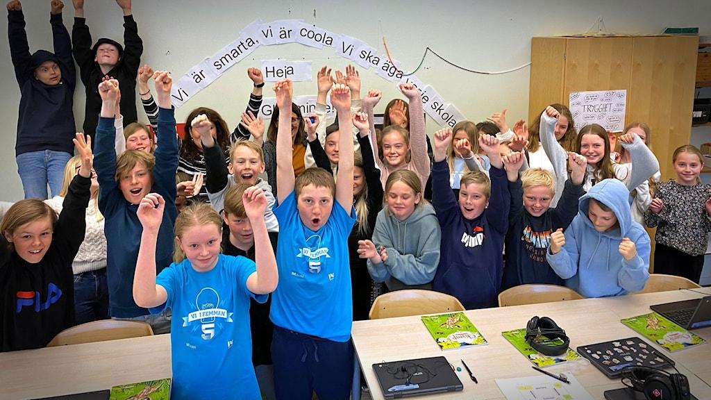 En skoklass står i ett klassrum och ser glada ut.