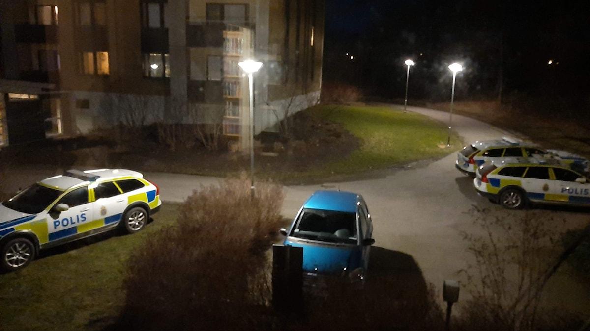 Polisbilar uppställda utanför ett lägenhetshus.