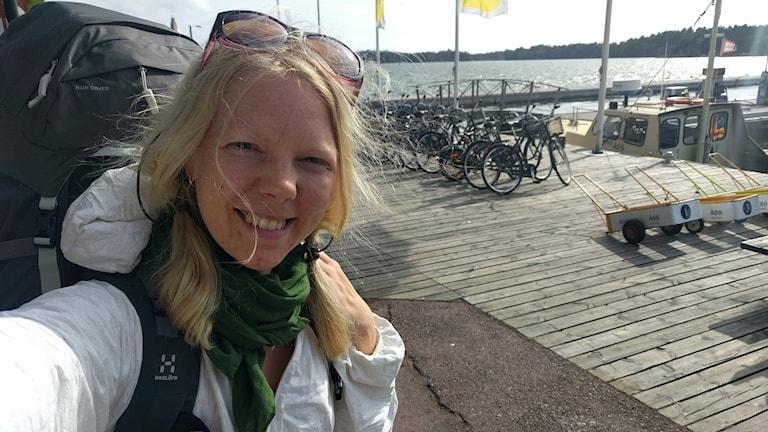 Frida Löfquist  på en solig brygga med vatten i bakgrunden.
