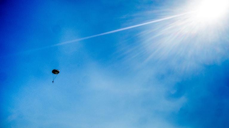 En fallskärmshoppare på lång avstånd mot blå himmel