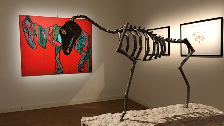 Mager häst i armeringsjärn i förgrund och röd målning i bakgrund.