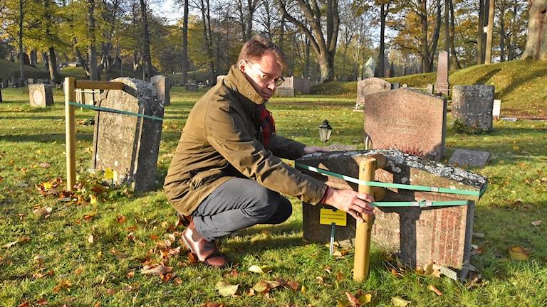 EN kyrkogårdschef som stabiliserar upp ostadiga gravstenar.