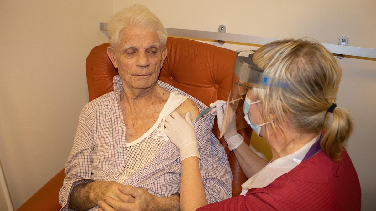En person får en spruta i armen.