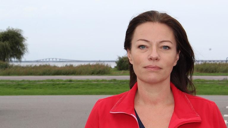 Matilda Wärenfalk med röd jacka och med Ölandsbron i bakgrunden