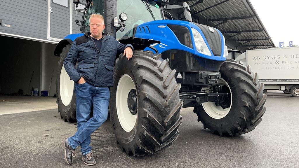 En bild på en man som står med armen lutad mot en blå traktor.