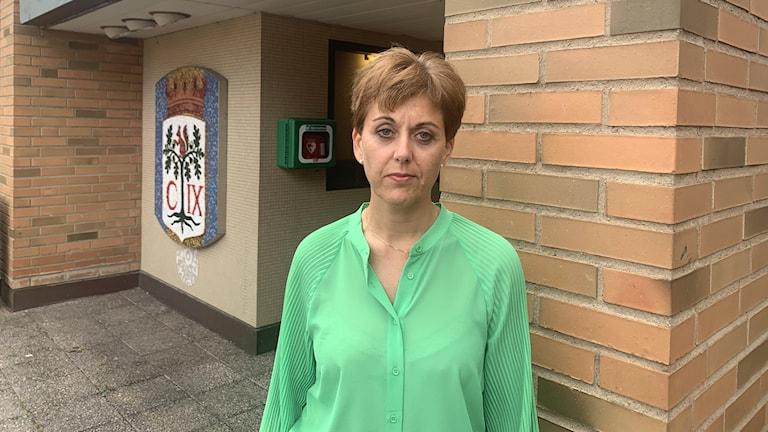 En kvinna framför ett hus. Hon har grön tröja.
