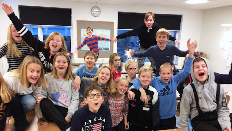 Elever som jublar i ett klassrum.