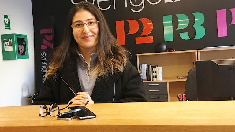 En kvinna sitter framför en bänkskiva med glasögon och mobiler på.