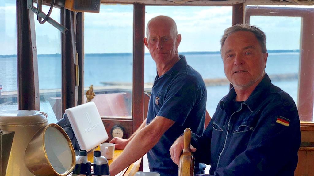 två besättningsmän på bryggan ombord på lastfartyg