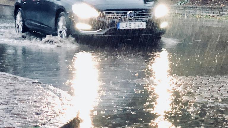 Bil som kör på översvämmad väg.