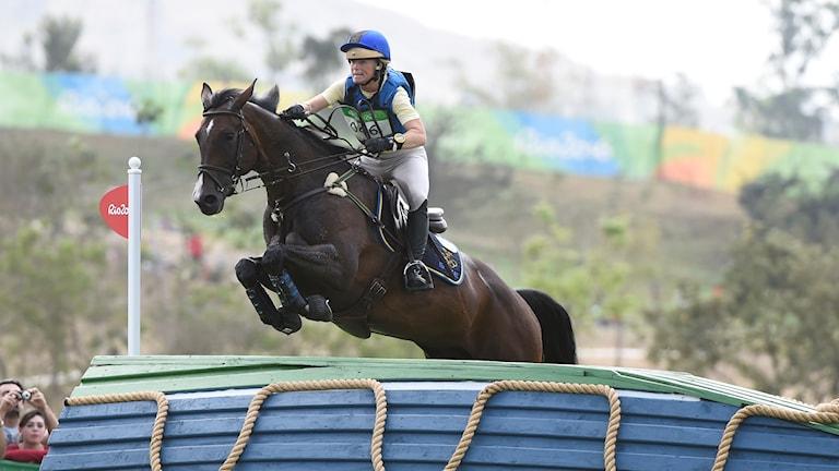 Sara Algotsson Ostholt på häst, hoppandes över ett hinder.