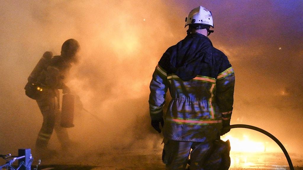 Brandmän som släcker en bilbrand.
