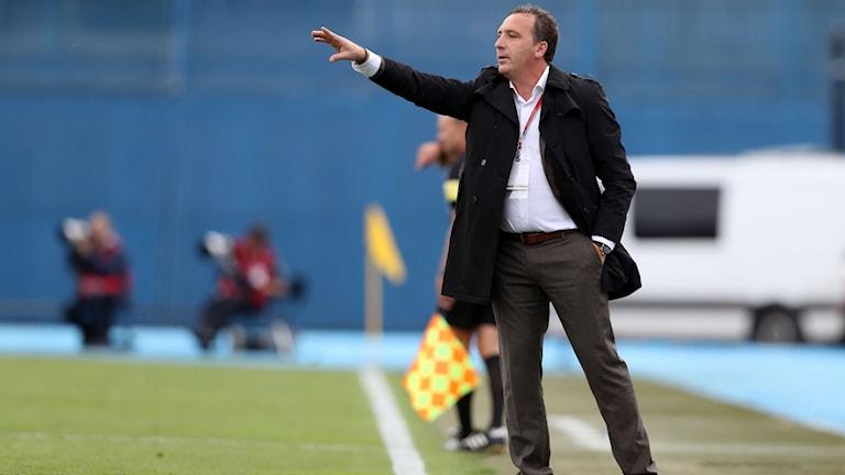 Albert Bunjaki står vid sidlinjen på en fotbollsplan.