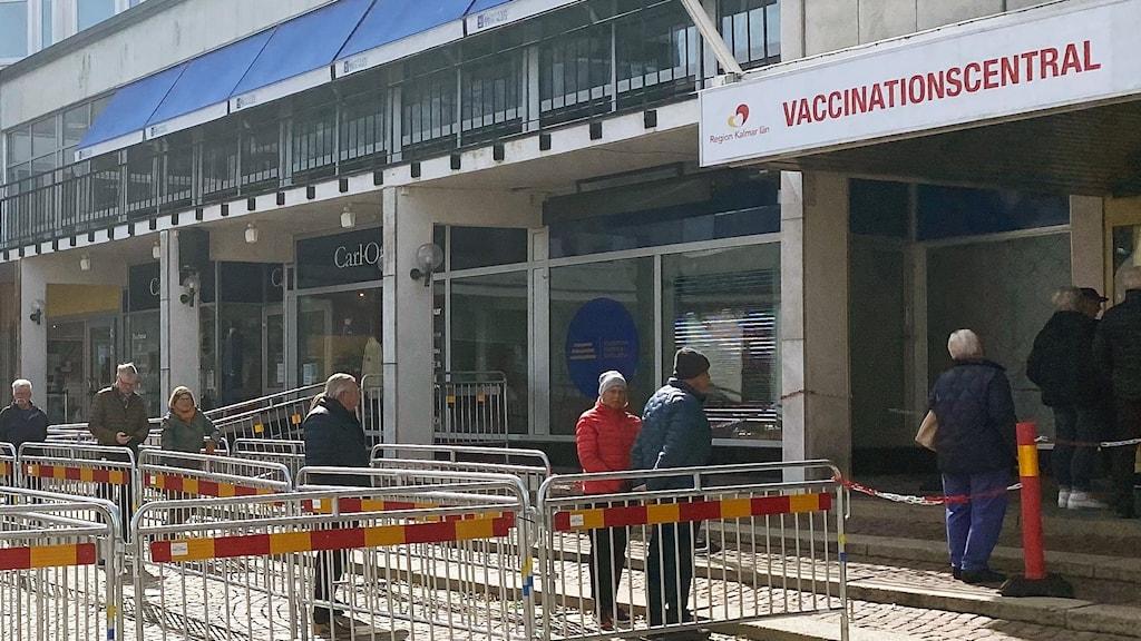 Bild över ett torg där flera människor köar till en vaccinationscentral.