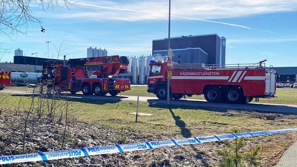 Två brandbilar, vitt och blått avspärrningsband och byggnader i bakgrunden.