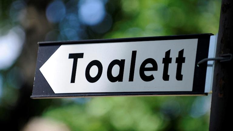 """Skylt med texten """"toalett""""."""