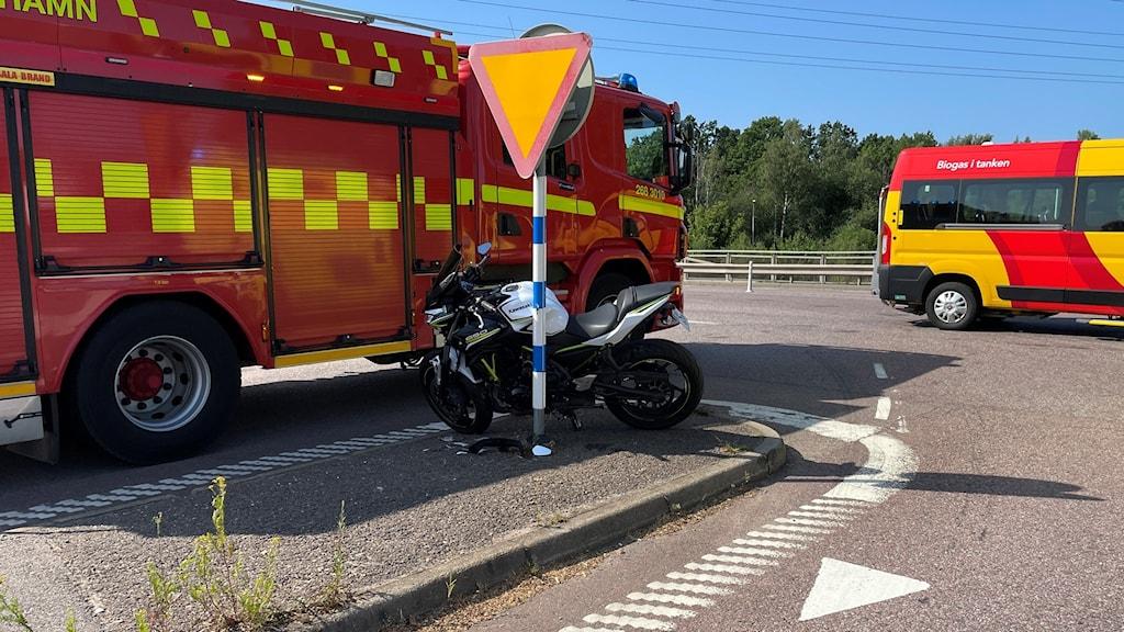 Ett räddningsfordon och en kvaddad motorcykel i en korsning.