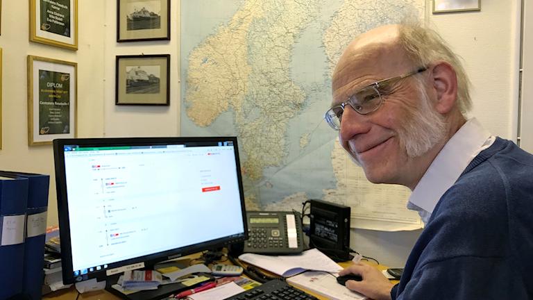 En man med grå polisonger och glasögon sitter vid en dator.