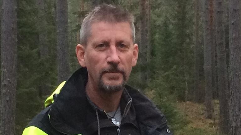 Ove Arnesson står i en skog med mycket tall.