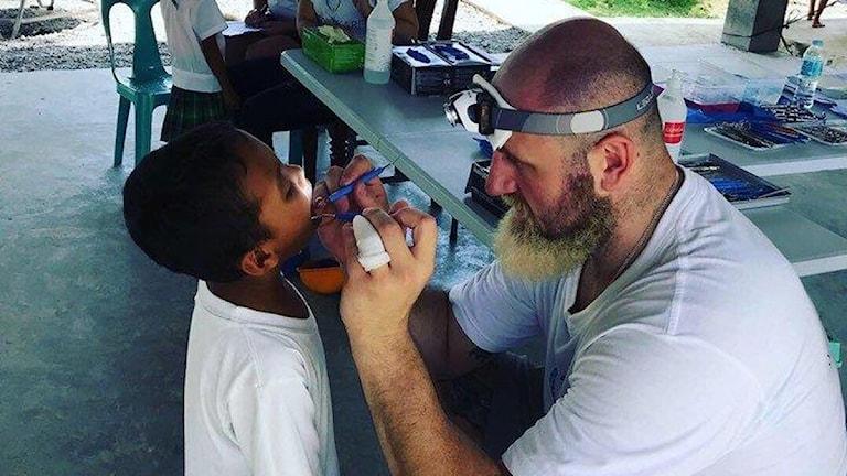 En tandläkare tittar i ett barns mun.