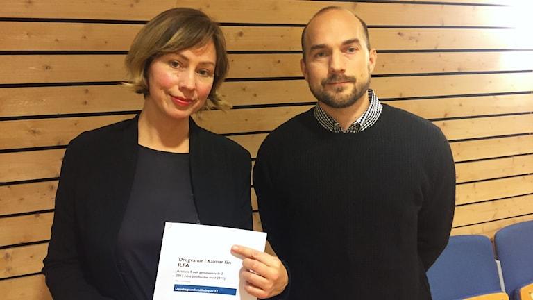 Clara Henriksson och Olof Emilsson framför en trävägg. Clara håller i ett papper.
