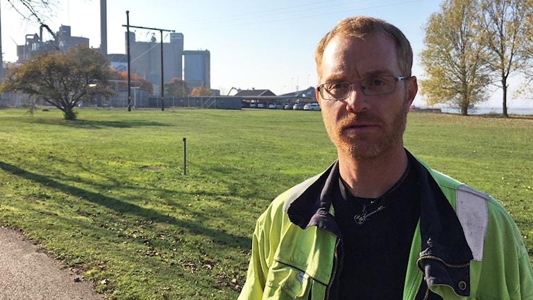 Johan Persson framför en fabriksbyggnad.