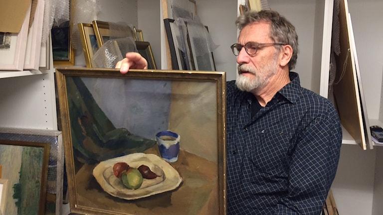 Jörgen Platzer tittar på ett gammalt konstverk