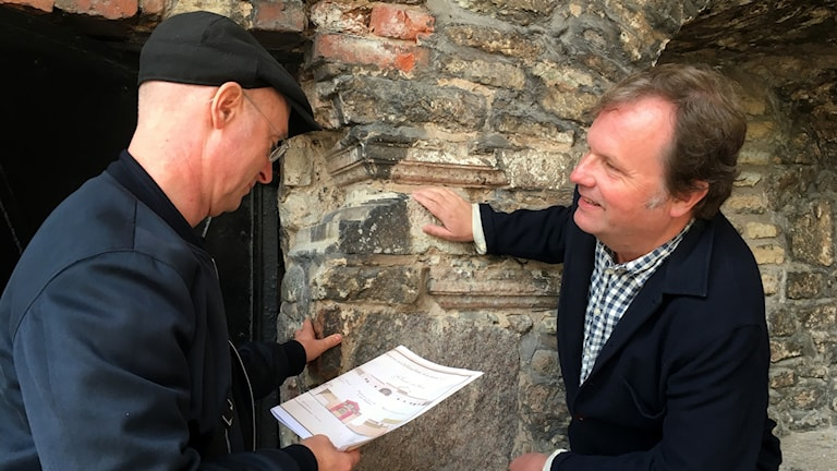 Mur med två män framför