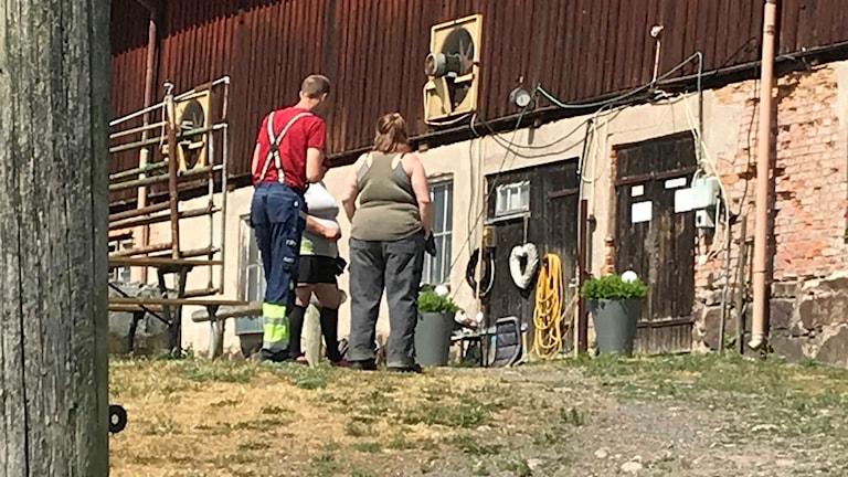På fotot syns några personer vid en ladugård.
