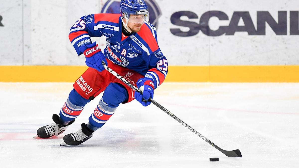 Ishockeyspelare i rink under pågående match.