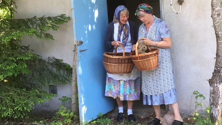 Två äldre damer framför ett gammalt fryshus.