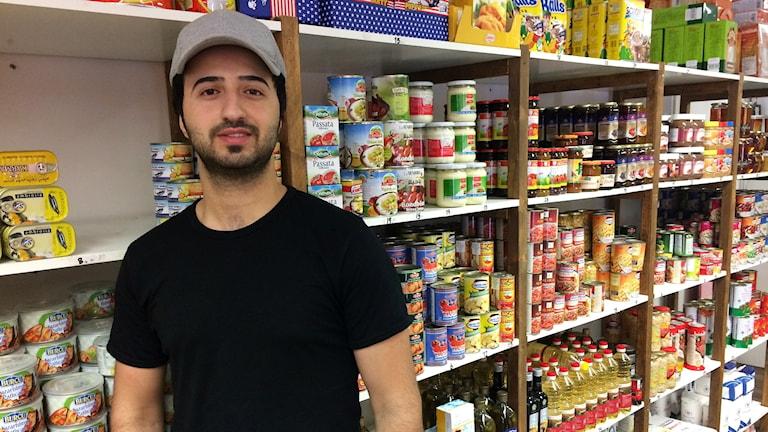 Yasser Algoanea framför varor i sin butik.