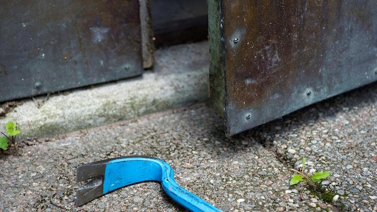 En blå kofot ligger på marken utanför en dörr på glänt.