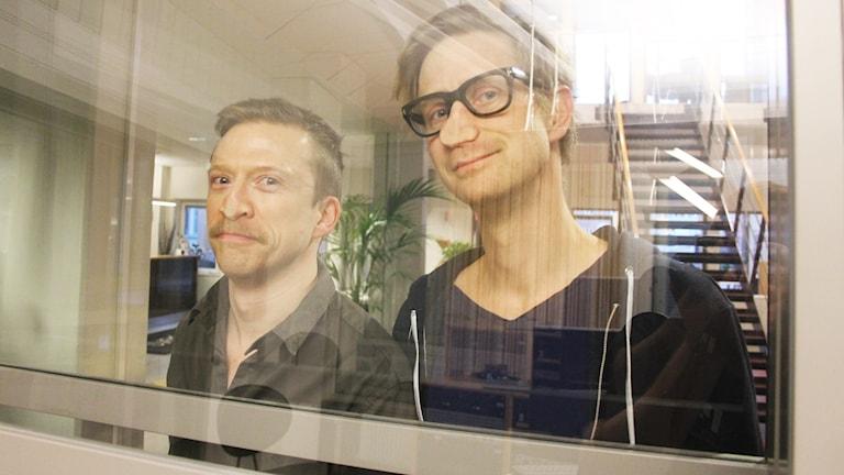 Måns Nilsson och Anders Johansson trycker ansiktena mot en glasruta.