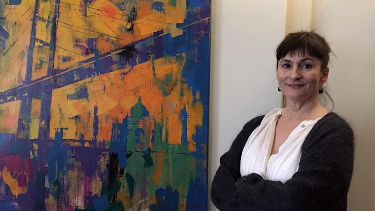 Rúna í Baianstovu, lektor i socialt arbete på Örebro Universitet står jämte en abstrakt målning. Hon har svart uppsatt hår och svarta örhängen.