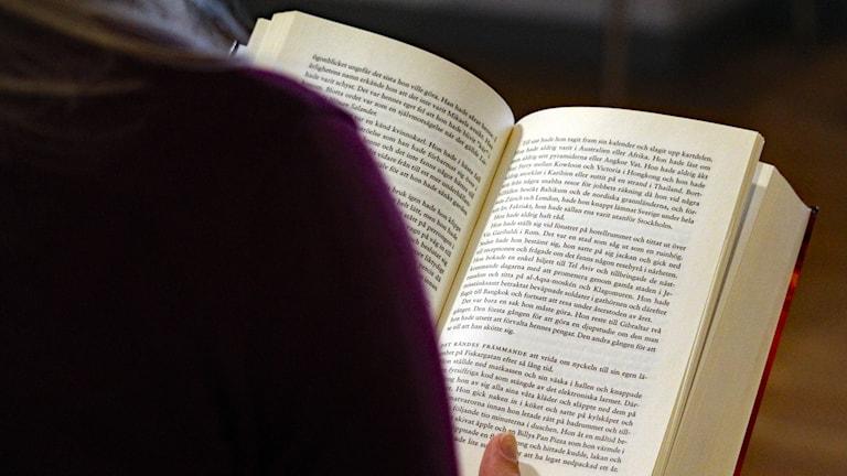 En person sitter och läser. Bilden visar en person över axeln som sitter och läser.