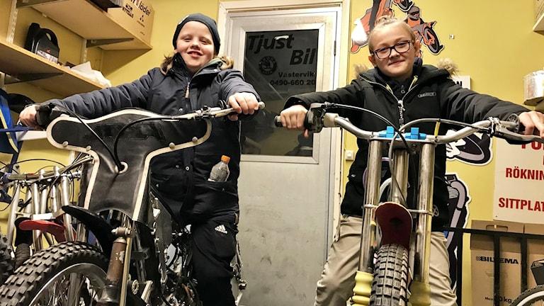 Två unga killar som sitter på speedwaycyklar.