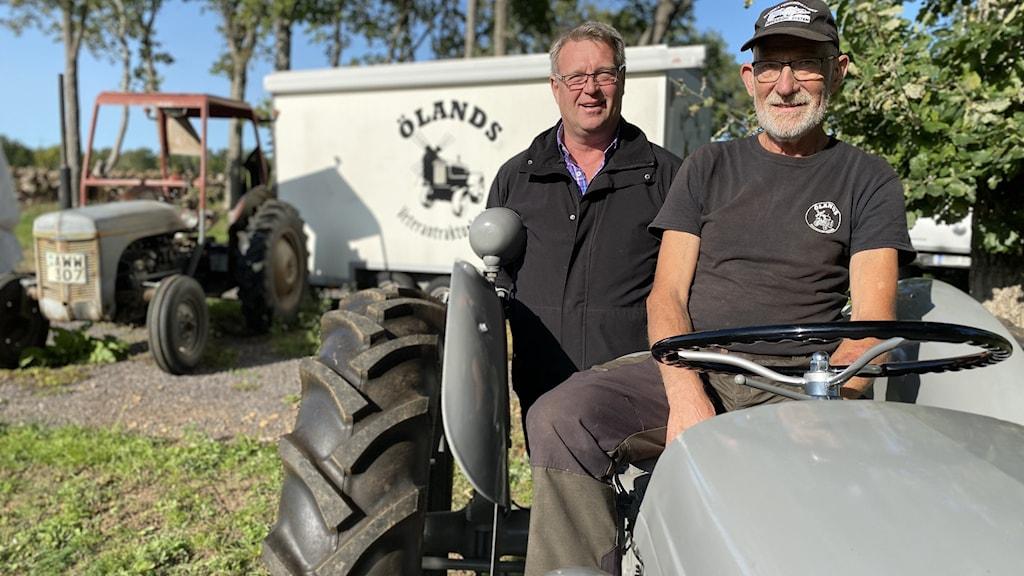 Två äldre män vid en grå traktor med öppen hytt.