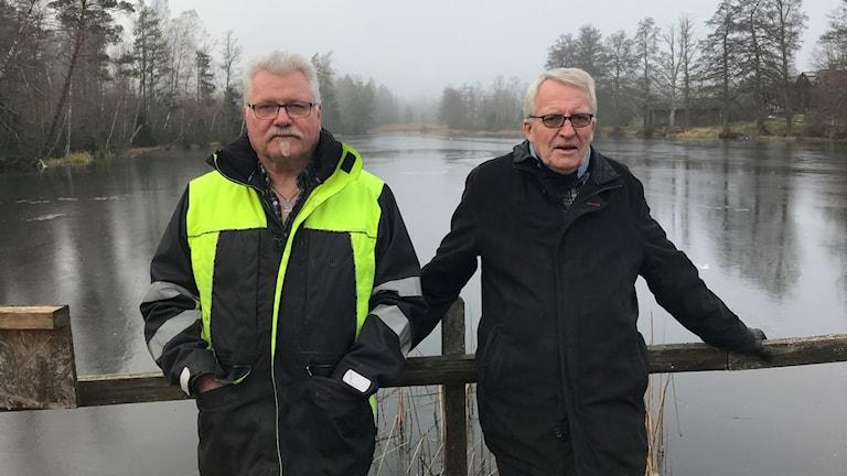 Kjell Hallenquist och Anders Lagerman framför en damm